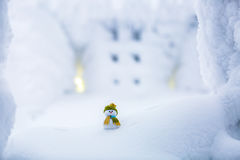 Un petit bonhomme de neige dans un chapeau et une écharpe Images libres de droits