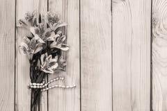 Un petit bouquet d'Alstroemeria avec un fil de perle sur un fond en bois Photographie stock libre de droits