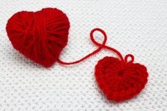 Un petit coeur fait main rouge de crochet et une boule rouge de fil comme un coeur sur le fond blanc de crochet Un coeur fait de  Image stock