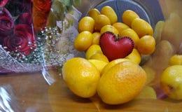 Un petit coeur rouge sur de petites oranges dans la bouteille en verre sur le plancher en bois Images stock