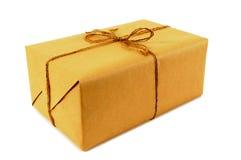 Un petit colis ou paquet de papier brun attaché avec de la ficelle d'isolement sur le blanc photo libre de droits