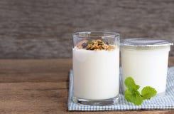 Un petit déjeuner de yaourt avec des fruits secs a mis dessus une table en bois photos libres de droits