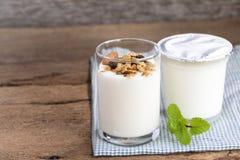 Un petit déjeuner de yaourt avec des fruits secs a mis dessus une table en bois Photographie stock
