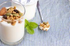 Un petit déjeuner de yaourt avec des fruits secs a mis dessus une table en bois Photo libre de droits