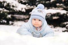 Un petit enfant dans des combinaisons bleues se trouvant sur la neige près des arbres de Noël photographie stock libre de droits