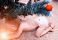 Un petit enfant dans une couche-culotte regarde sous le cadeau merveilleux rougeoyant d'arbre, magique pendant la nouvelle année, images stock