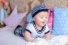 Un petit enfant doux dans une chemise rayée et des chapeaux se trouvant sur le divan dans la chambre photographie stock libre de droits