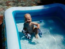 Un petit enfant s'assied dans la piscine et les sourires, jeux, le soleil brille l'?t? images stock
