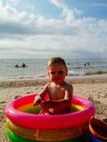Un petit enfant s'assied dans la piscine et les sourires, jeux, le soleil brille l'?t? photos libres de droits