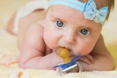 Un petit enfant tient une tétine dans sa main Photographie stock libre de droits