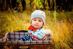 Un petit enfant triste s'asseyant dans une valise dans la forêt d'automne images stock