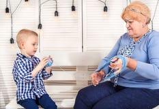 Un petit petit-fils aide la grand-mère à enrouler le fil dans un embrouillement photographie stock