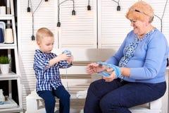 Un petit petit-fils aide la grand-mère à enrouler le fil dans un embrouillement image stock