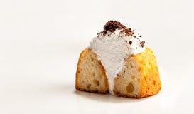 Un petit gâteau bourré de la crème blanche a coupé dans la moitié, d'isolement sur le fond blanc L'image avec l'espace de copie Photographie stock