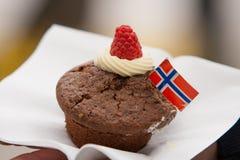 Un petit gâteau de chocolat avec le drapeau norvégien sur une serviette blanche 17 mai Photographie stock