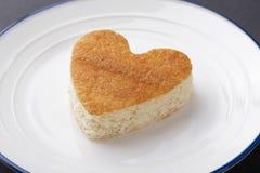 Un petit gâteau en forme de coeur d'un plat blanc avec une frontière bleue image libre de droits