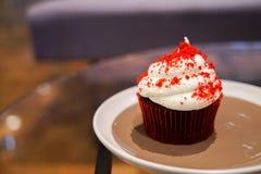 Un petit gâteau rouge de velours dans un plat sur le Tableau en verre images libres de droits