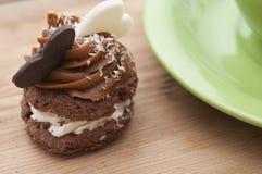 Un petit gâteau sur une table avec deux coeurs de chocolat Image stock