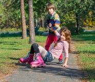 Un petit garçon élève sa soeur qui est tombée sur des patins de rouleau Image libre de droits