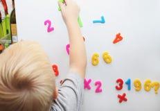 Un petit garçon étudie les nombres magnétiques sur le réfrigérateur Formation d'élève du cours préparatoire image stock