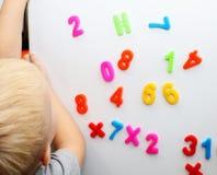 Un petit garçon étudie les nombres magnétiques sur le réfrigérateur Formation d'élève du cours préparatoire photos stock