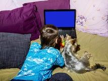 Un petit garçon avec un petit chien regardant un ordinateur portable Images libres de droits