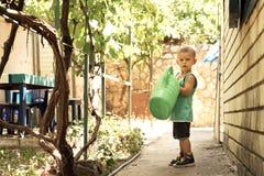Un petit garçon avec une grande boîte d'arrosage verte est dans la cour L'aide de la grande mère images libres de droits