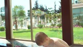 Un petit garçon blond s'enveloppe dans une serviette après la natation dans la piscine banque de vidéos
