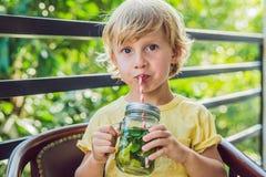Un petit garçon boit l'eau avec la menthe et la chaux Buvez plus d'eau c photo stock