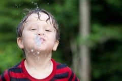 Un petit garçon crache l'eau Image stock