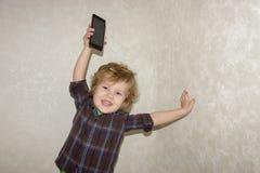 Un petit garçon d'enfant en bas âge prend un instrument de smartphone au-dessus de sa tête images libres de droits