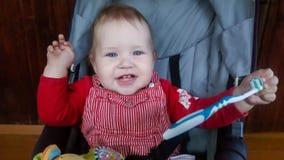 Un petit garçon d'enfant en bas âge s'assied dans une poussette et joue avec une brosse à dents image stock