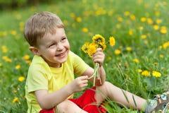 Un petit garçon dans un pré complètement des pissenlits image stock