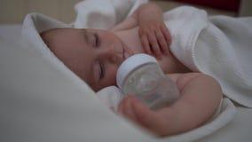 Un petit garçon de sommeil tient une bouteille dans le mouvement lent banque de vidéos