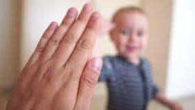 Un petit garçon donne joyeusement cinq à un adulte à l'intérieur au ralenti clips vidéos