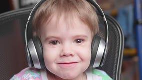 Un petit garçon drôle s'assied dans une chaise et écoute la musique par des écouteurs Haut proche de visage Photo stock