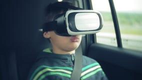 Un petit garçon emploie un casque pour un casque de réalité virtuelle banque de vidéos