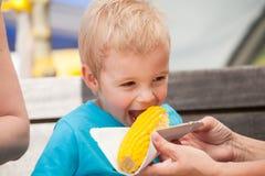 Un petit garçon et un épi de maïs Images libres de droits