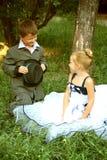 Un petit garçon et une fille dans une scène romantique Image libre de droits