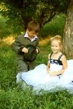 Un petit garçon et une fille dans une scène romantique Image stock