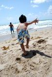 Un petit garçon exécutant dans l'océan images stock