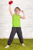 Un petit garçon exécute un exercice avec des haltères L'enfant serre sa main, le biceps Sport, mode de vie sain Photo stock