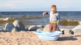 Un petit garçon joue avec le sable et les poires sur l'océan étayent clips vidéos