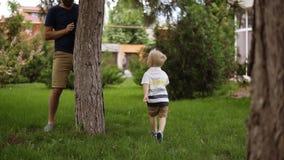 Un petit garçon joue avec son père dans le cache-cache dans le jardin Il court heureusement sur l'herbe Le père clips vidéos