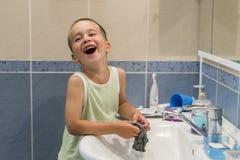 Un petit garçon lave des vêtements dans la salle de bains Photos stock