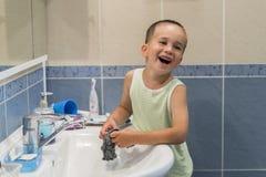 Un petit garçon lave des vêtements dans la salle de bains Photo stock