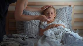 Un petit garçon malade dans un lit La mère l'embrasse et mesure sa température Concept de grippe de bébé banque de vidéos