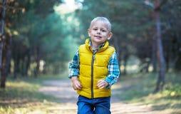 Un petit garçon marche le long d'un chemin forestier photos libres de droits