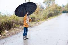 Un petit garçon marche pendant l'automne de parapluie de pluie image libre de droits