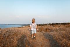 Un petit garçon mignon marchant avec ses parents sur une banque d'une rivière sur un fond brouillé naturel Photos stock